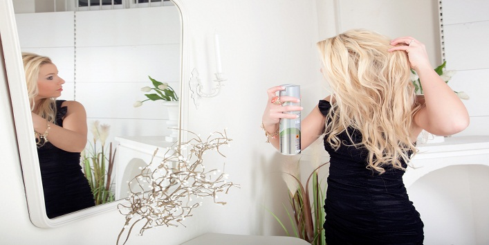 Beautiful young blond woman standing in front of a mirror spraying hairspray on her long hair in preparation for an evening out