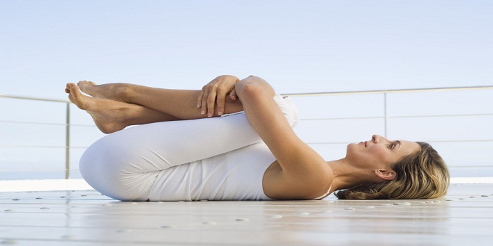 Woman practicing yoga on deck