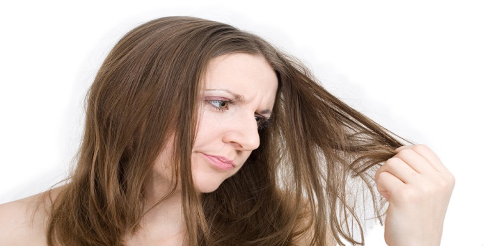 Woman dissatisfied with her hair holding them in hand