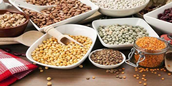 arrangement of various legumes in bowls on table