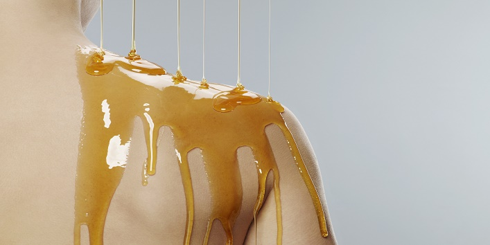 strands of honey dripping onto girls shoulder