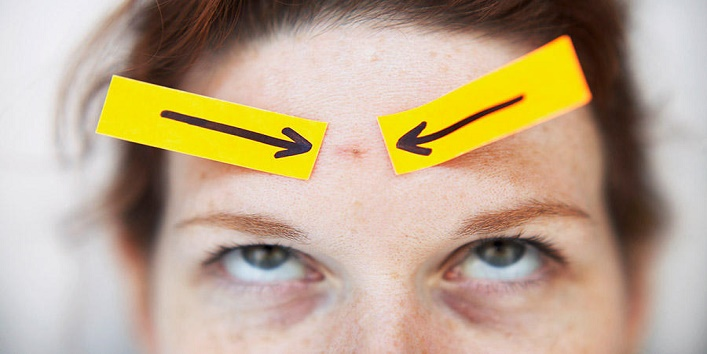 Arrows Pointing to Blemish on Woman's Forehead