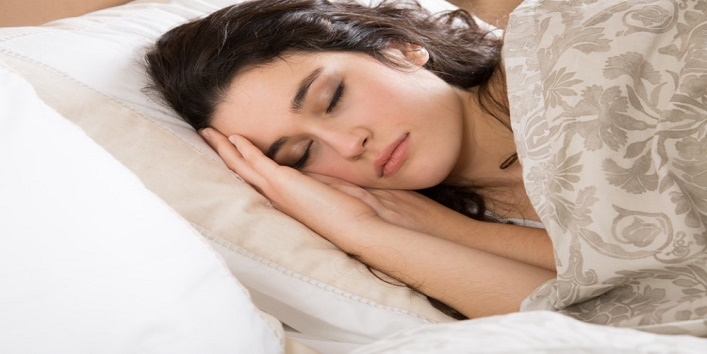 Young brunette woman sleeping in bed covered with a beige flowered quilt