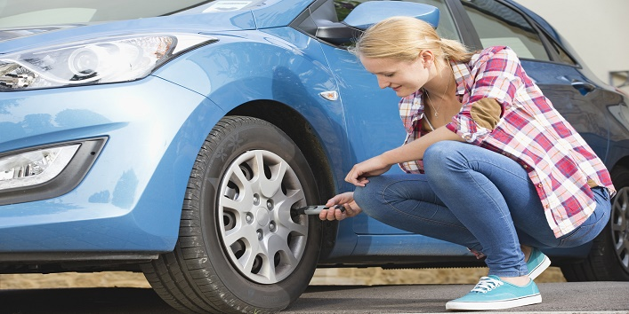 Woman Checking Tyre Pressure On Car