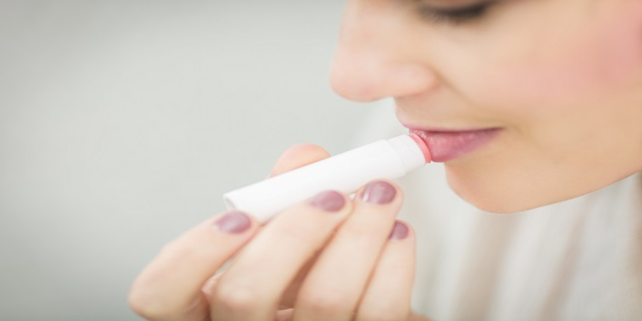 Applying lip balm before applying matte lipstick