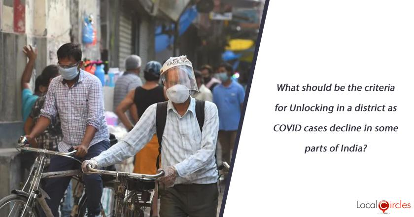 What should be the criteria for Unlocking in a district as COVID cases decline in some parts of India?