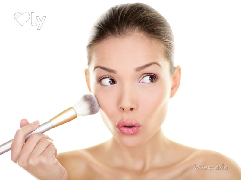 Girl Applying Blush To Cheekbones