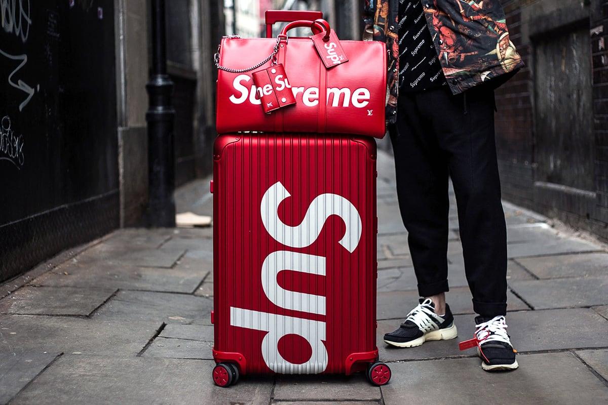 un sac supreme posé sur une valise supreme rouge. A coté un homme debout dans une ruelle on ne voit que le bas de son corps