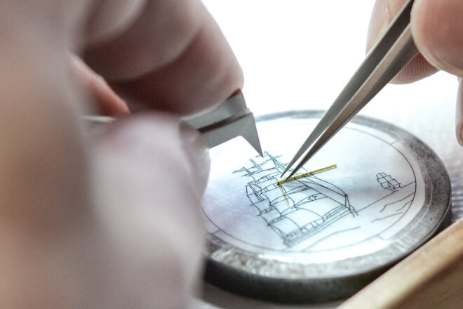 Wires are shaped and attached to a dial to form cells, before enamel is painted in