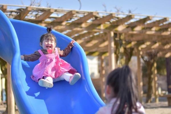 孩子玩溜滑梯時,家長應在一旁陪伴,看著孩子溜下來。