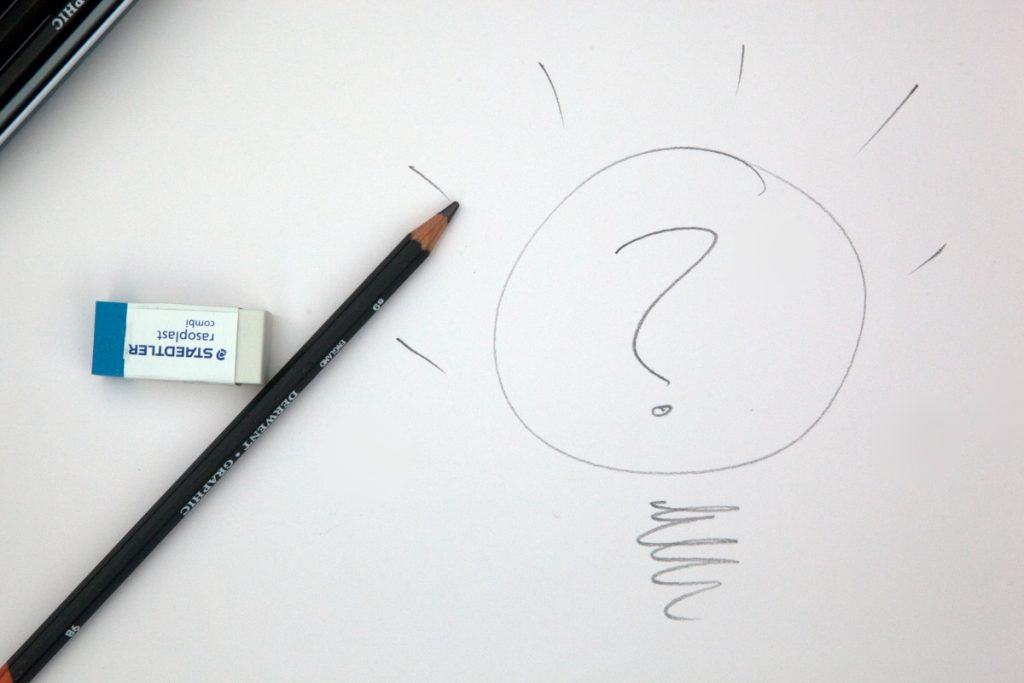 Pencil and paper with a question mark