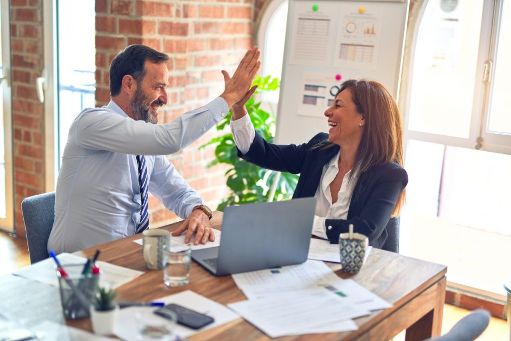 An image of two managers in an office giving each other a high five to illustrate internal stakeholders.