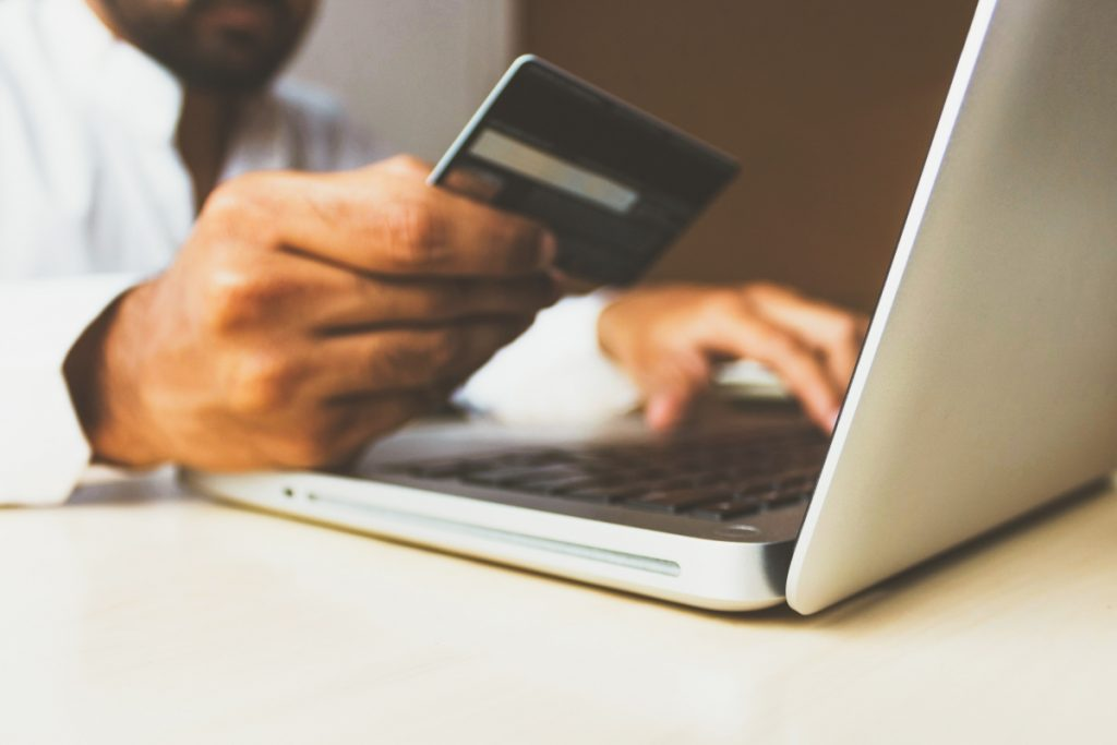 Man holding a credit card next to a laptop showing ecommerce in action