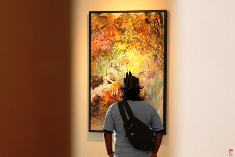 """Pengunjung sedang mengapresiasi karya Lini Natalini Widhiasi berjudul """"Sawah"""". Foto: (doc/GNI-Jatiari)"""