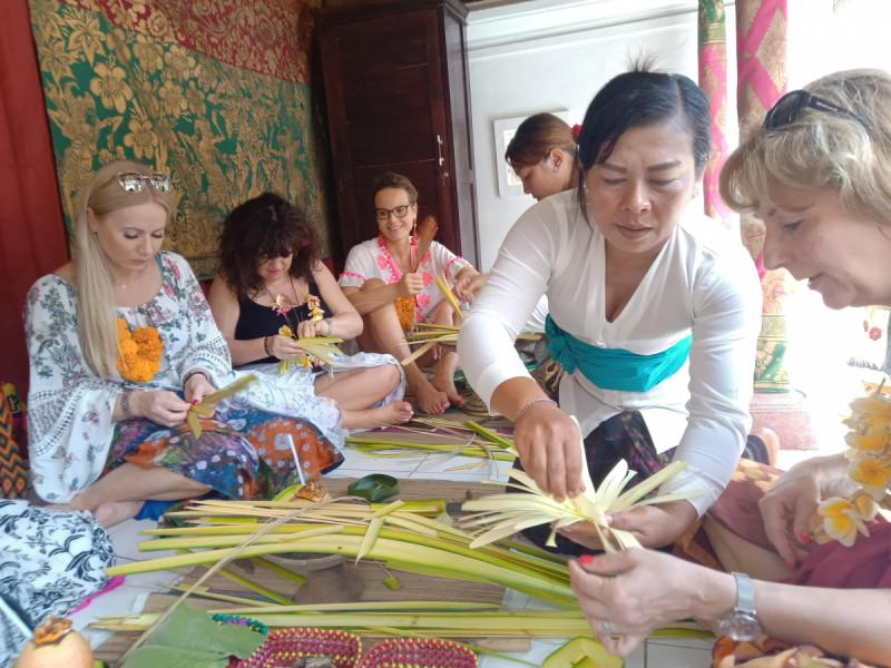 Ibu Desa Sangketan mengajarkan turis Jinawi cara membuat canang. Foto: Yusrina.