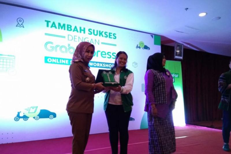 Kepala Dinas Koperasi UKM Pemkot Makassar Evy Aprialti, menerima plakat dari Head of GrabExpress, Tyas Widyastuti di Makassar, Selasa (10/12/19). (Foto: Suriani Mappong)