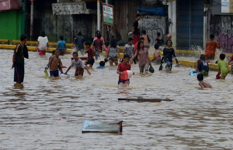 Anak-anak bermain air saat banjir menggenangi Jalan Jatinegara Barat, Jakarta, Kamis (2/1/2020). (Foto: Imam Buhori)