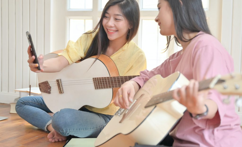 Teenage girls and friends playing guitar and using a smartphone video call.