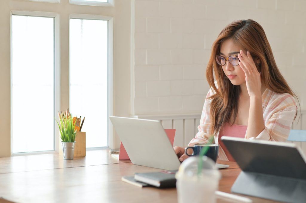 Girl student holding the glasses carefully while looking at laptop to prepare for graduate studies.
