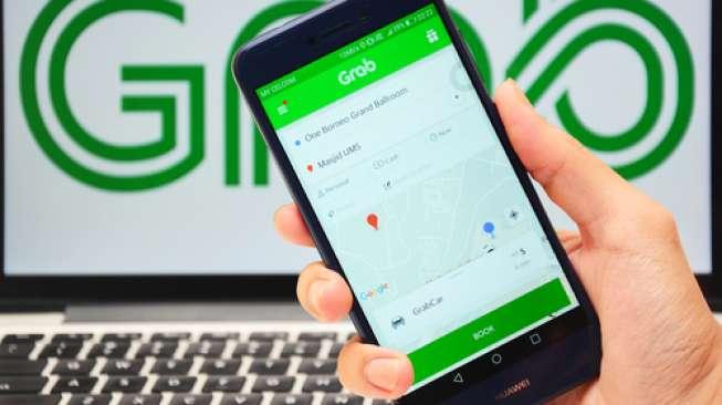 Aplikasi layanan transportasi online Grab pada sebuah ponsel dan komputer. [Shutterstock]