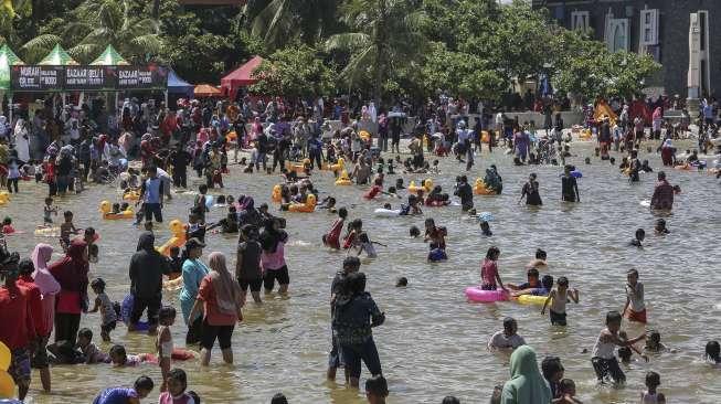 Peneliti BRIN menemukan kandungan parasetamol di perairan Ancol dan Angke di Teluk Jakarta. Foto: Pengunjung memadati kawasan wisata Pantai Ancol, Jakarta, Senin (25/12). [Suara.com]