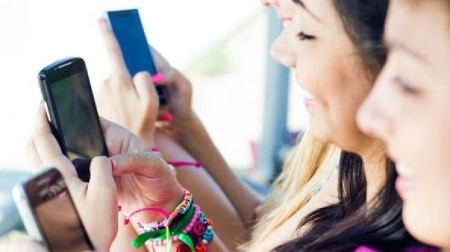 Beberapa perempuan sedang menatap layar ponsel. (Shutterstock)