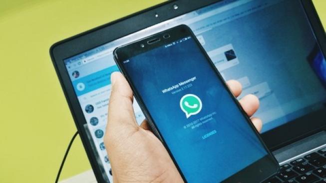 Ilustrasi WhatsApp di sebuah ponsel dan laptop. [Shutterstock]