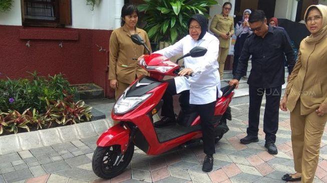 Wali Kota Surabaya, Tri Rismaharini atau Ibu Risma, semangat menjajal sepeda motor listrik warna merah [Suara.com/Dimas Angga Perkasa].