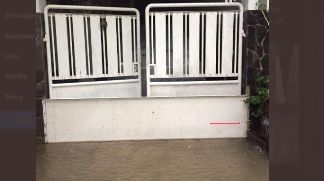 Pintu air sederhana mampu menahan air banjir masuk ke dalam rumah. (Twitter/@dinidini).