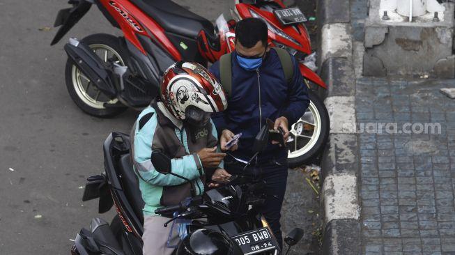Pengemudi ojek online menurunkan penumpang di kawasan Palmerah, Jakarta, Selasa (7/4). [Suara.com/Angga Budhiyanto]