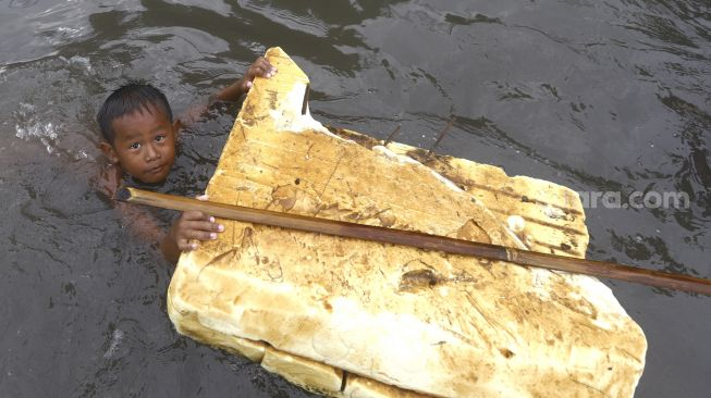Bocah berenang saat banjir rob di kawasan Pelabuhan Nizam Zachman, Muara Baru, Jakarta Utara, Jumat (5/6). . [Suara.com/Angga Budhiyanto]