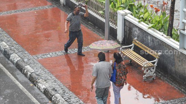 Pejalan kaki melintas ditengah hujan di Jalan Sudirman, Jakarta Pusat, Selasa (9/6). [Suara.com/Alfian Winanto]