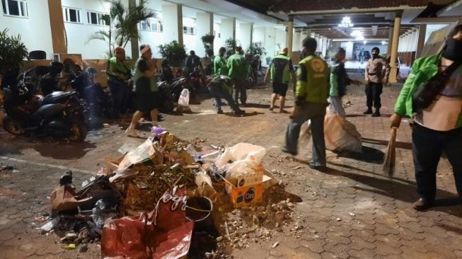 Sejumlah relawan ojek online membersihkan halaman kantor DPRD DIY pasca bentrok, Kamis (8/10/2020). [Muhammad Ilham Baktora / SuaraJogja.id]