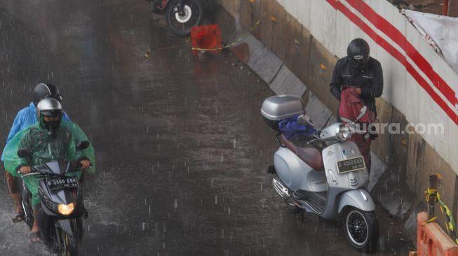 Seorang pengendara motor berteduh untuk mengenakan jas hujan di Jalan Gatot Subroto, Jakarta, Senin (26/10). [Suara.com/Alfian Winanto]