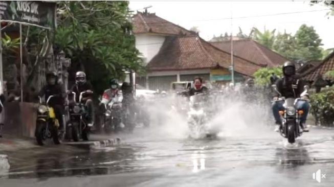 Emak-emak percaya diri terjang banjir di antara konvoi motor (Facebook)