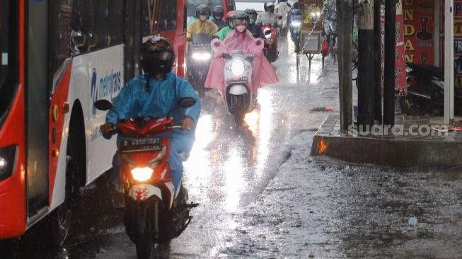 BMKG memperingatkan potensi La Nina di akhir 2021. Foto: Pengendara motor mengenakan jas hujan ketika melintas saat hujan deras di kawasan Pinang Ranti, Jakarta Timur, Jumat (18/6/2021). [Suara.com/Alfian Winanto]