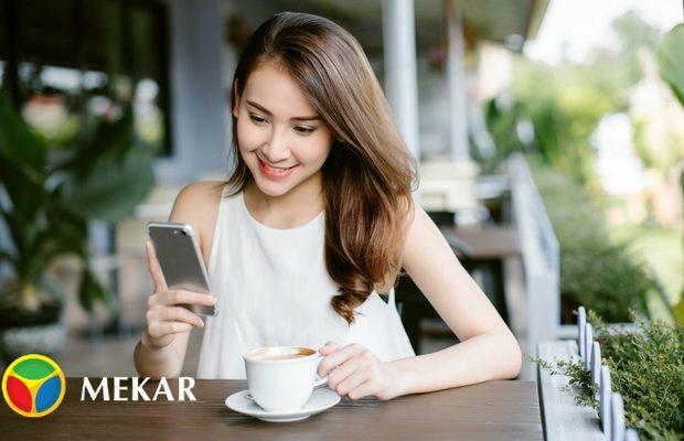 Wanita Tersenyum Saat Menatap Smartphonenya