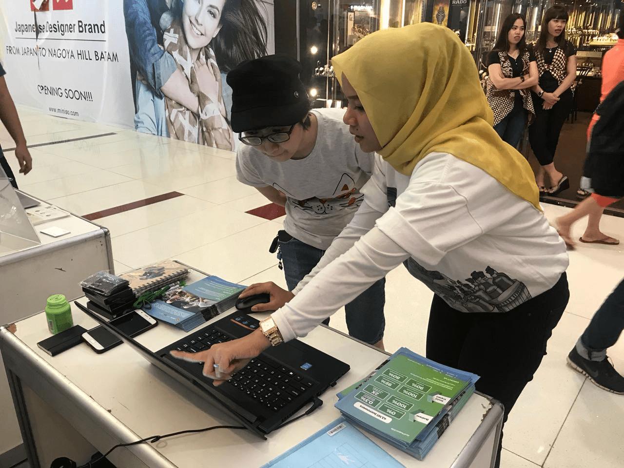 Relationship Manager Mekar, Yunita Anggraini Menjelaskan Produk Mekar Kepada Pengunjung Booth Mekar