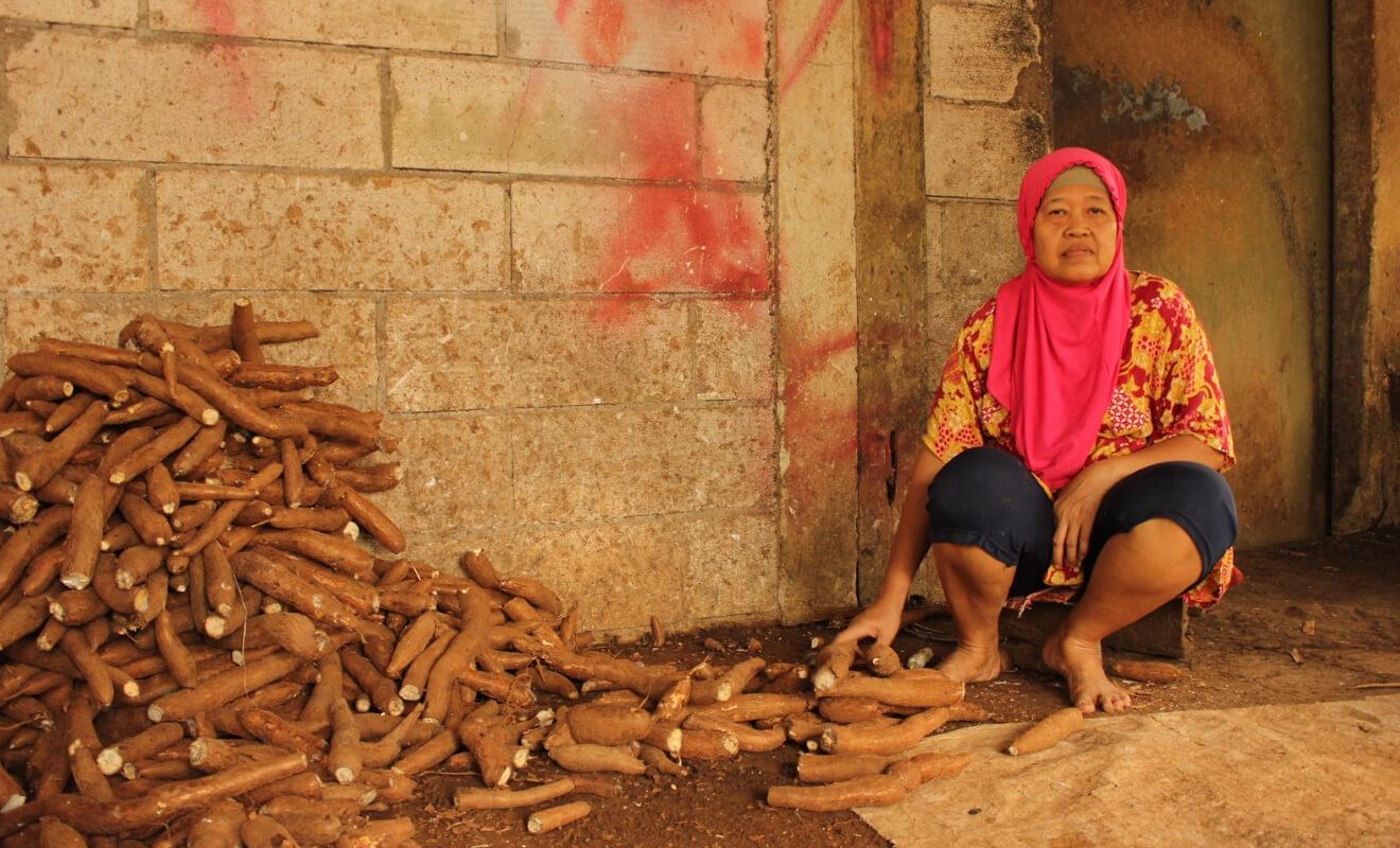 Seorang pekerja duduk dekat timbunan singkong yang belum dikupas di tempat produksi yang terletak tepat di sebelah rumah Usmini.