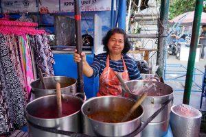 seorang-ibu-penjual-makanan-berdiri-sambil-tersenyum