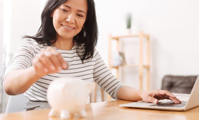 Wanita Paruh Baya Memasukkan Uang Koin Ke Dalam Celengan