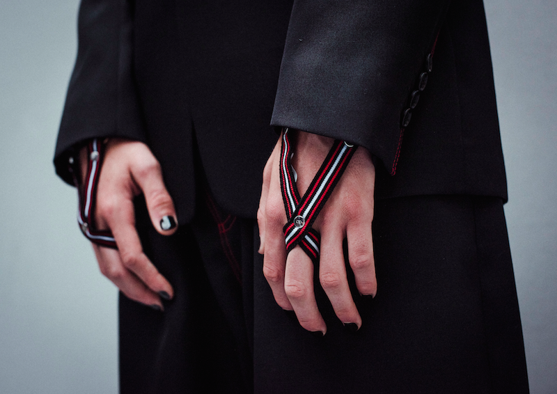 Black wool jackets with red topstitch details matched with red and white-striped ribbed cuffs for the hands, from Dior Homme's Summer 2017 collection. Photography by Morgan O'Donovan