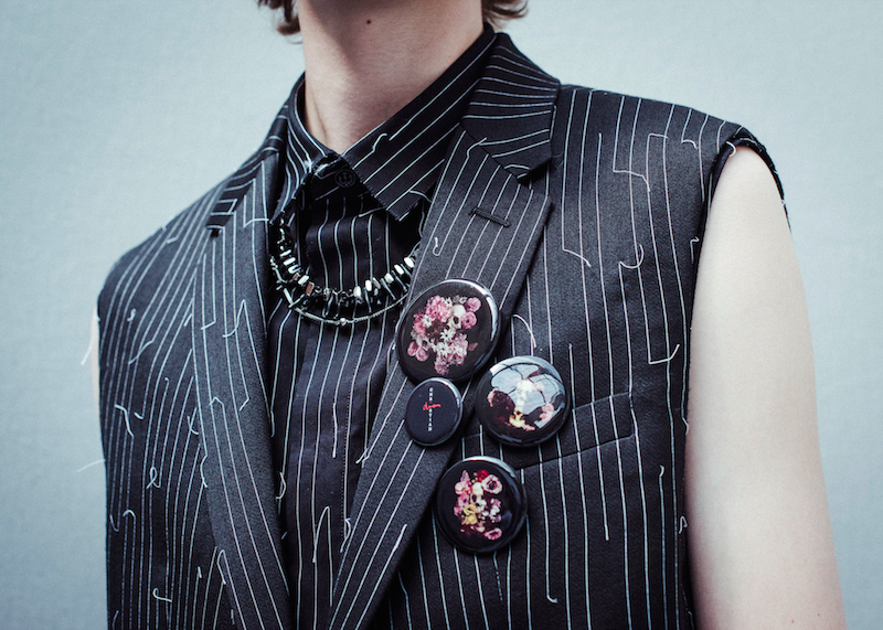 Black wool, silk and cotton two-button sleeveless jacket with steel badges in Dior Homme's Summer 2017 collection. Photography by Morgan O'Donovan