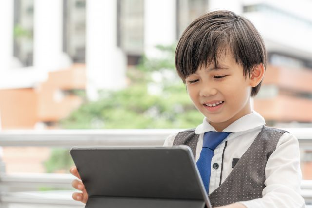young boy using smart phone tablet computer on business district urban, education concept