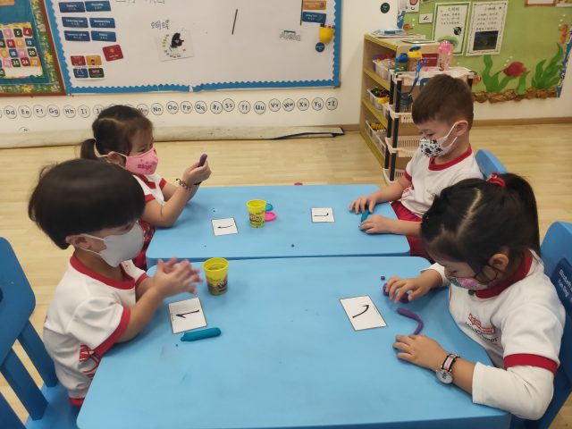 MindChamps PreSchool children learning the strokes of Chinese characters.