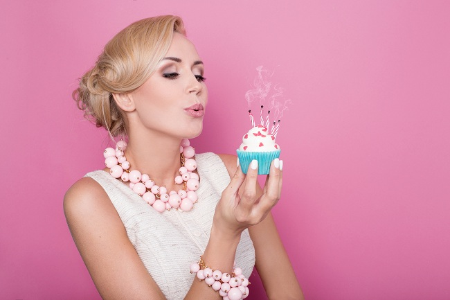 Beautiful women with cream dress holding small cake with colorfu