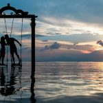 silhouette-of-young-couple-kissing-on-swing-at-sunset