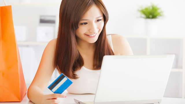 Young Woman Shopping Online With Credit Card And Laptop