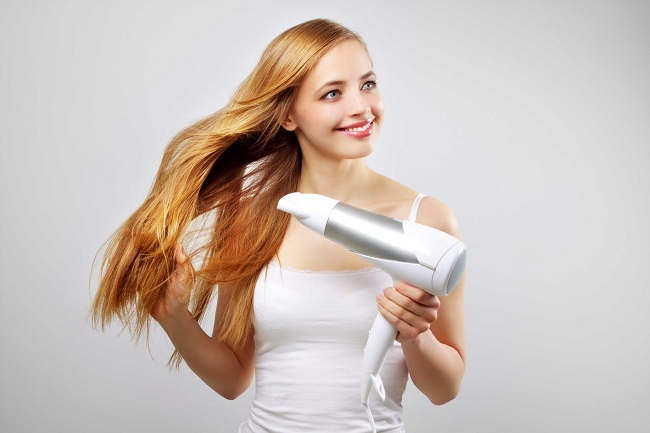 Beautiful smiling girl drying her hair with a blow dryer