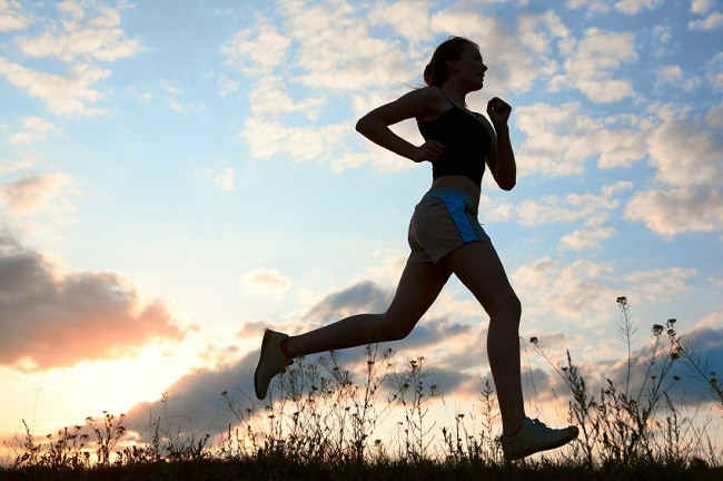 Silhouette woman run under blue sky with clouds